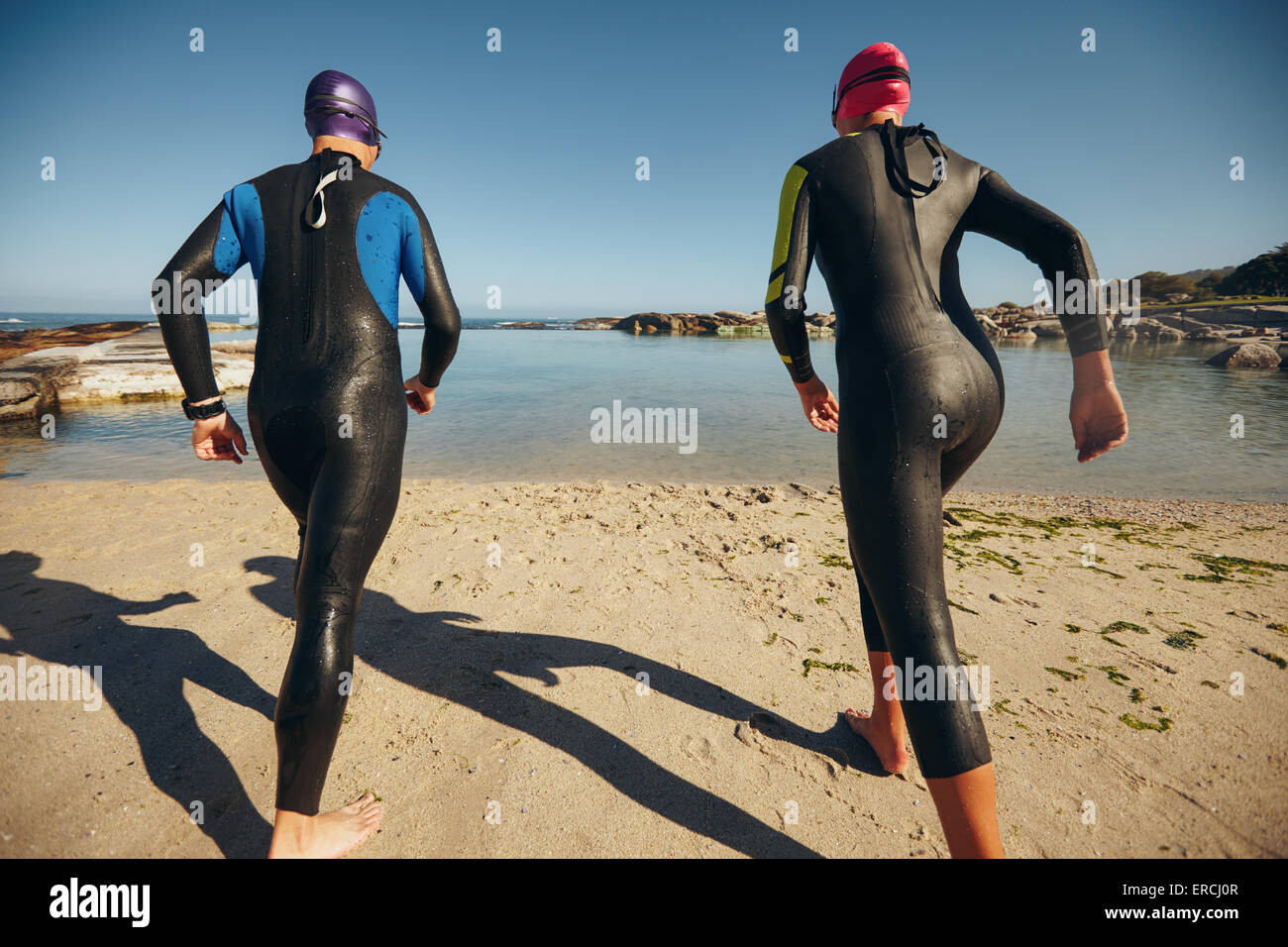 Rear view of triathlon participants ready to start of the race. Triathletes standing at the start line by the lake, - Stock Image