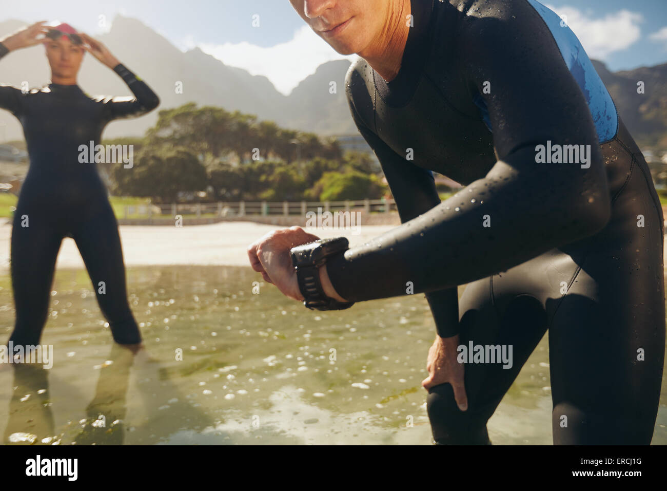 Man checking his timer. Athletes in wet suits preparing for triathlon competition. - Stock Image