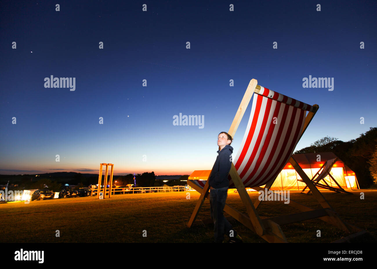 a boy looks up to the stars on a clear night whilst leaning against a giant deckchair - Stock Image