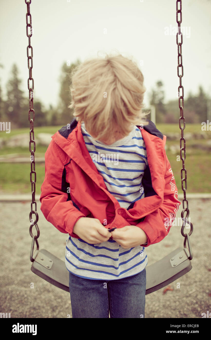 A young boy zips up his jacket before using the playground swing. - Stock Image