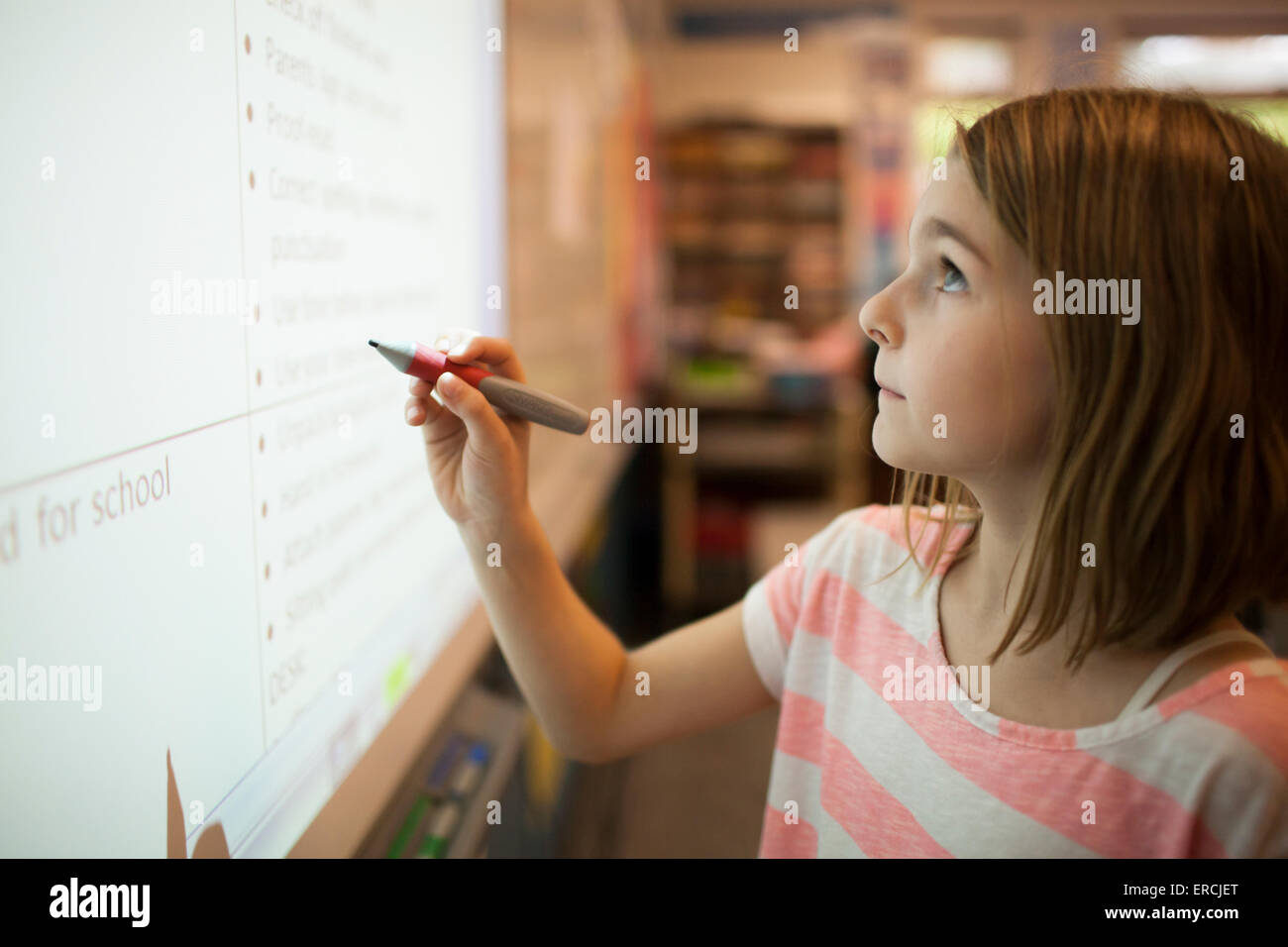 A young girl writting on a SMART Board - Stock Image