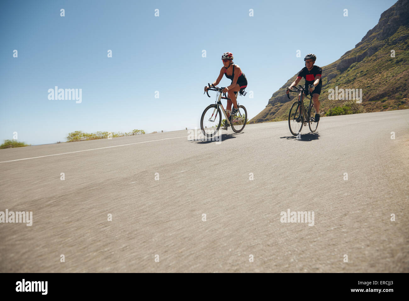 Athletes competing in the cycling leg of triathlon. Triathletes cycling on open country roads. Cyclist riding downhill. - Stock Image