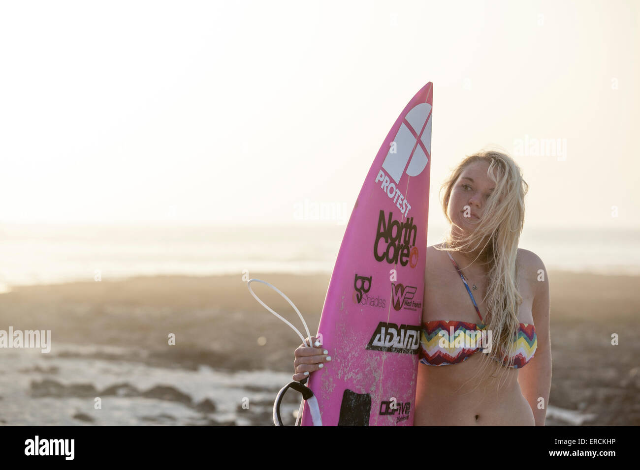 Blonde surfer girl standing alone on the beach at sunset with her surfboard - Stock Image