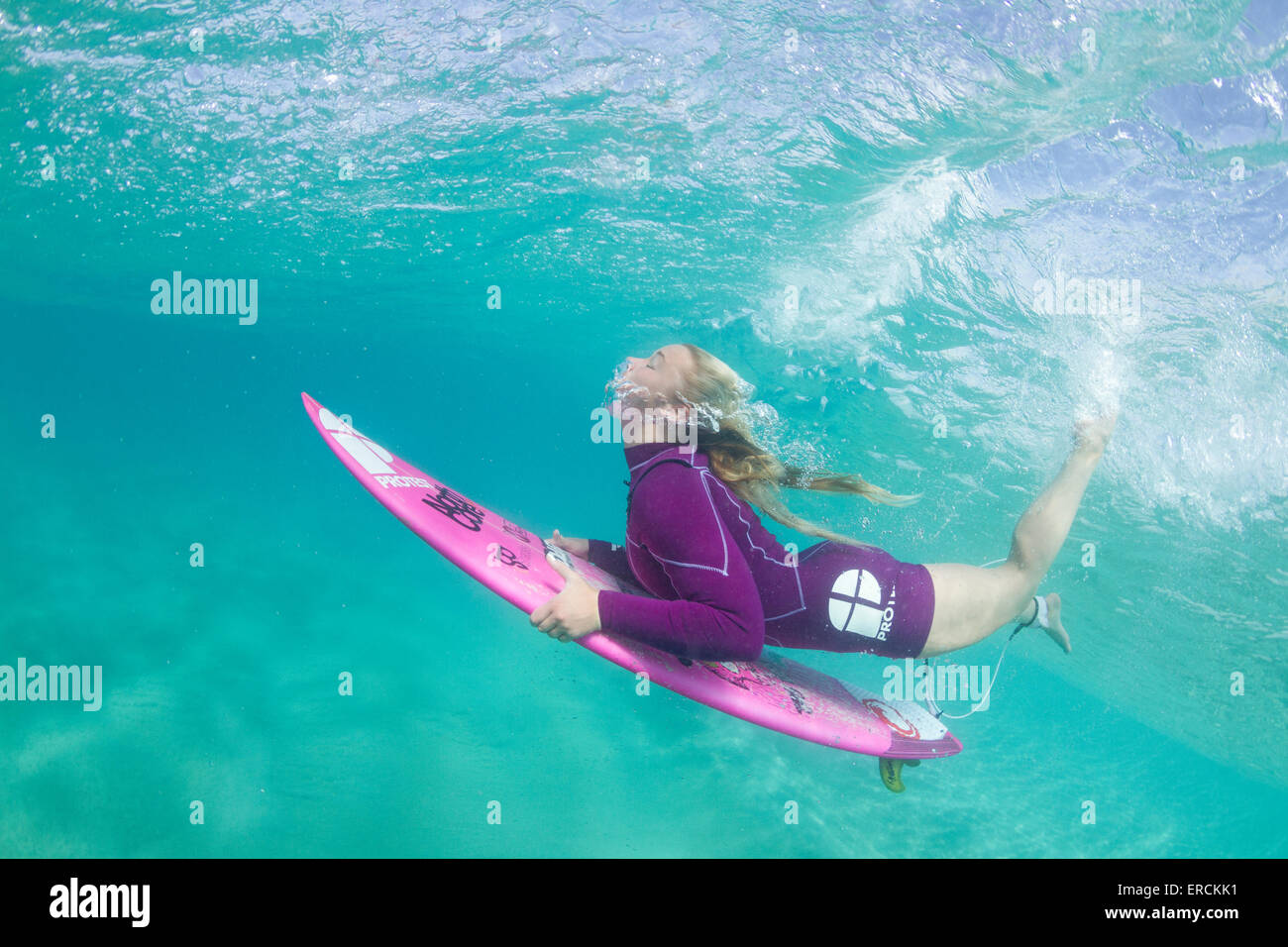 322c899ea0488 Underwater photo of a blonde surfer girl with a short wetsuit duck diving  under a wave