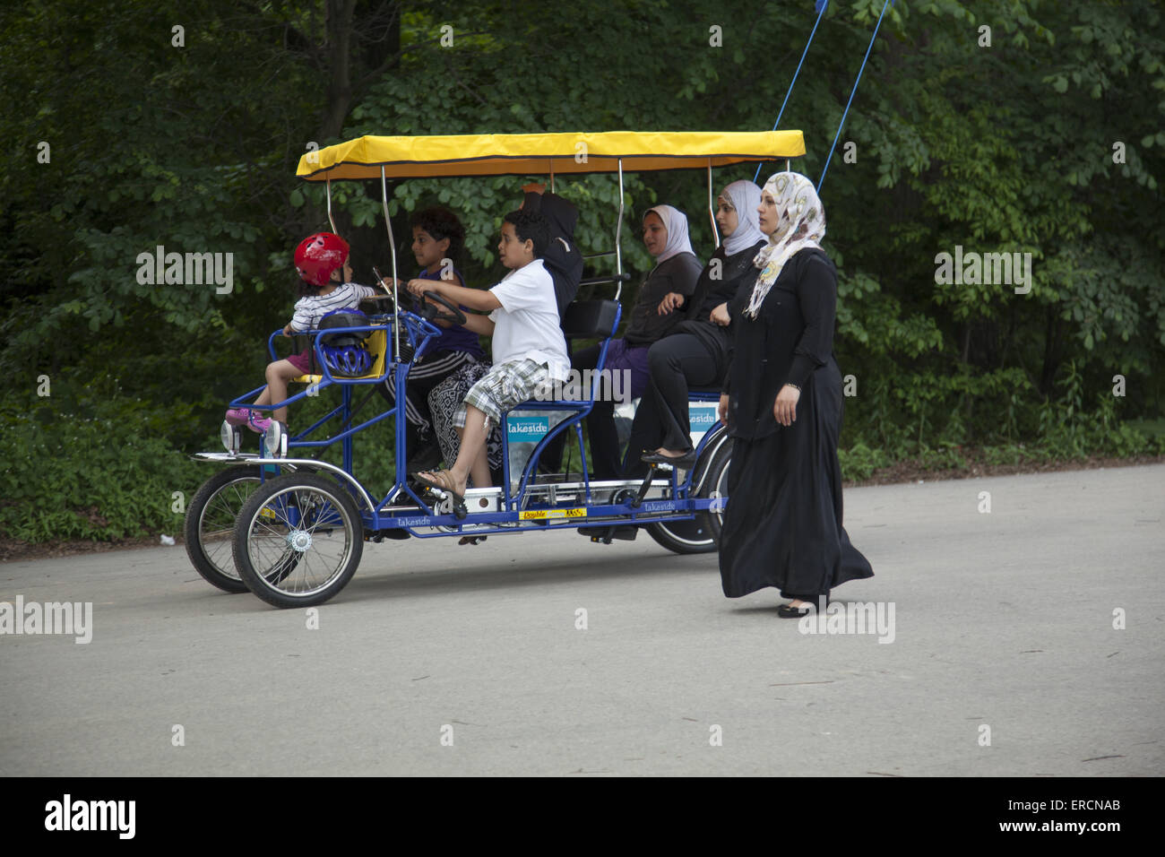 Muslim women with children have a nice time with a rented pedal surrey  in Prospect Park, Brooklyn, NY. - Stock Image