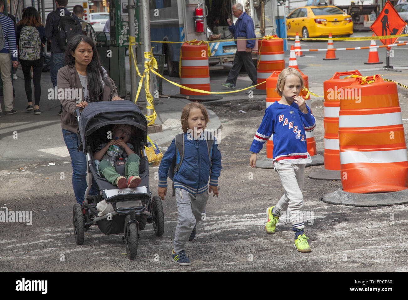 Children with nanny on their way home after school in the highly urban Tribeca neighborhood in Manhattan. - Stock Image
