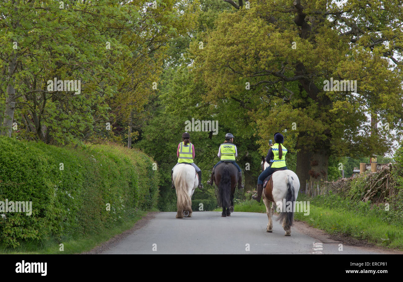 Female horse riders on a country lane with high visibility jackets, England, UK - Stock Image