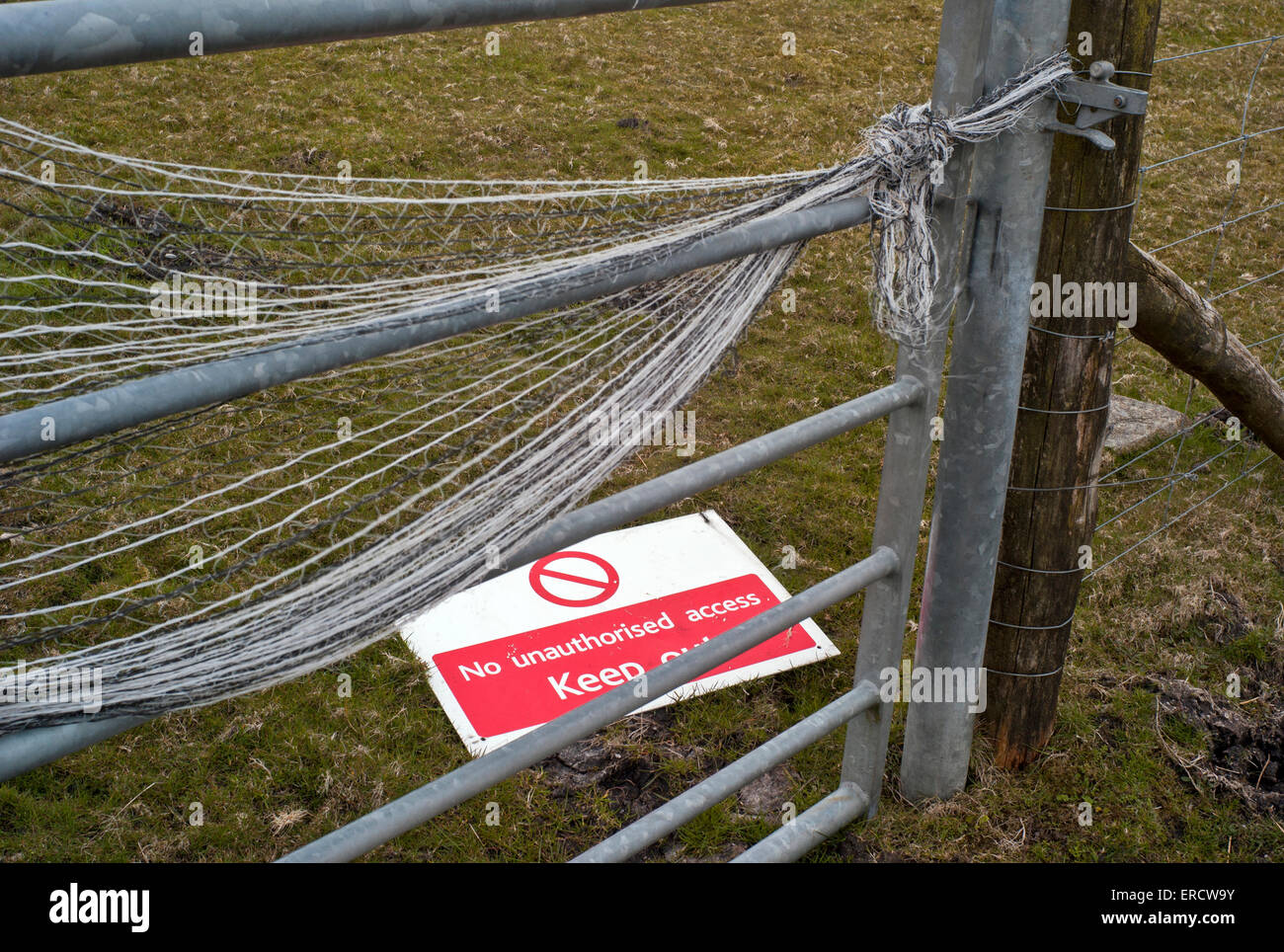 ''No unauthorized access Keep out'' sign by metal gate on moorland - Stock Image