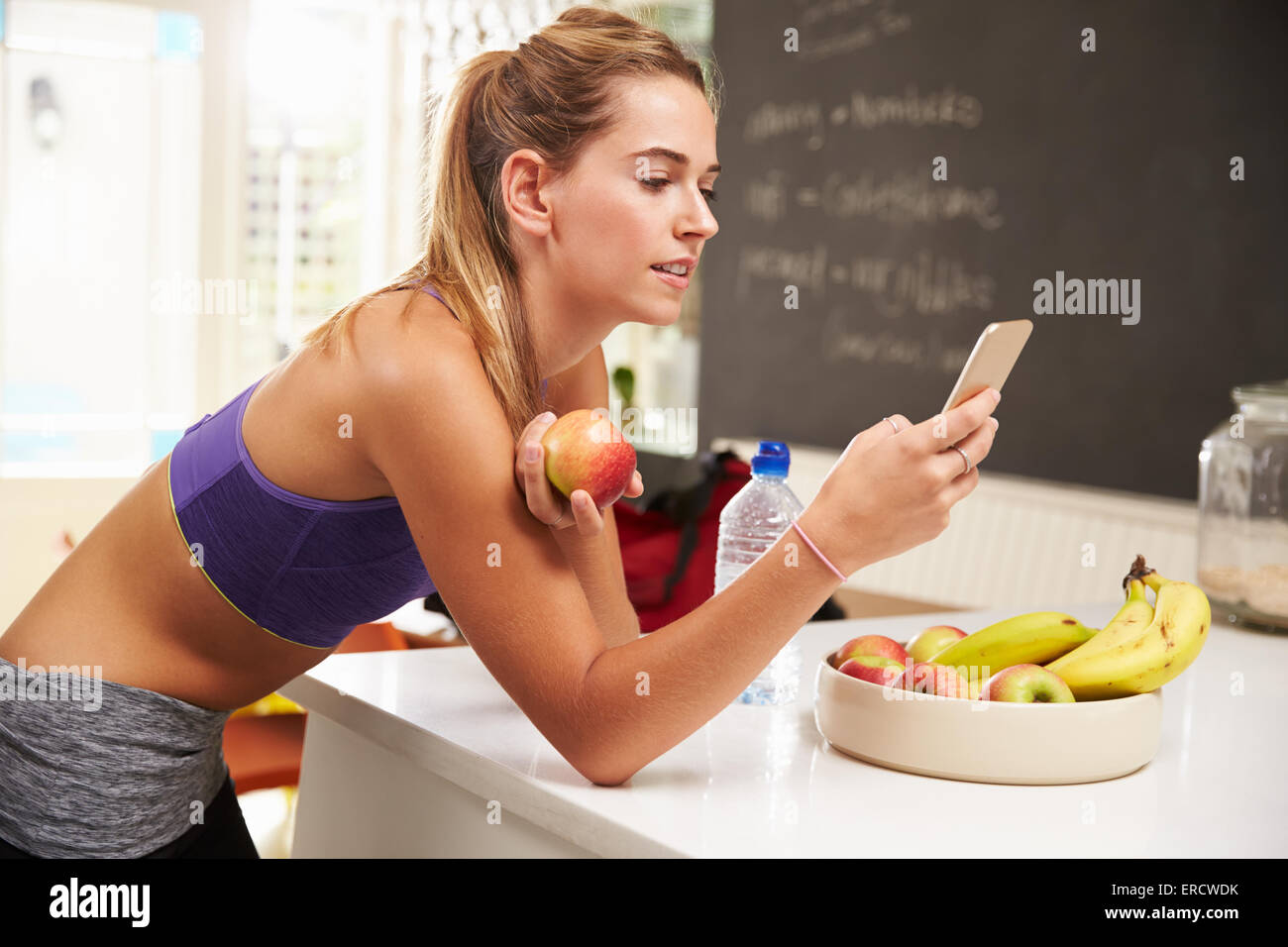 Woman Wearing Gym Clothing Looking At Mobile Phone - Stock Image