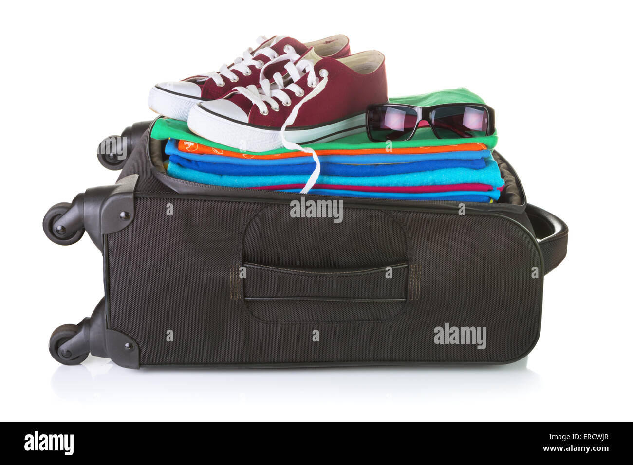 Ordinary wheeled black suitcase packed with bright summer clothes, sneakers, and sunglasses. Isolated on white - Stock Image