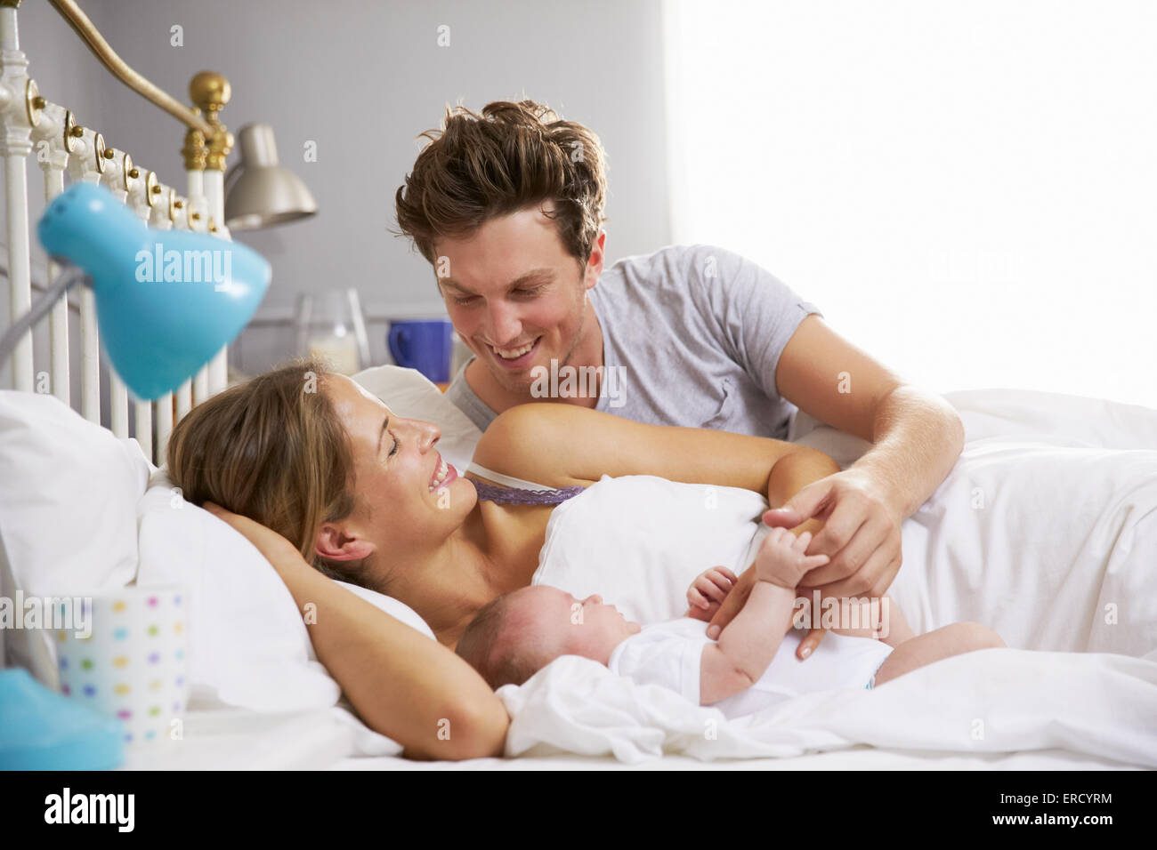 Family in bed holding sleeping newborn baby daughter