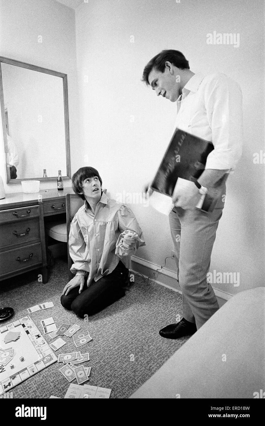 George Harrison speaks with Neil Aspinall while enjoying a game of Monopoly with singer songwriter Jackie de Shannon - Stock Image