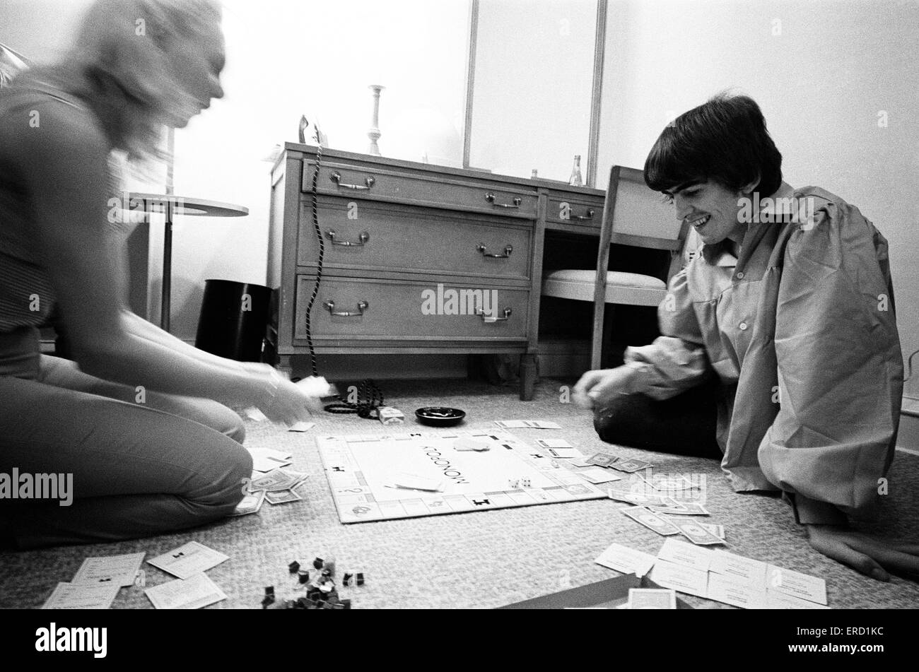 George Harrison enjoys a game of Monopoly with singer songwriter Jackie de Shannon, one of the tour's support - Stock Image