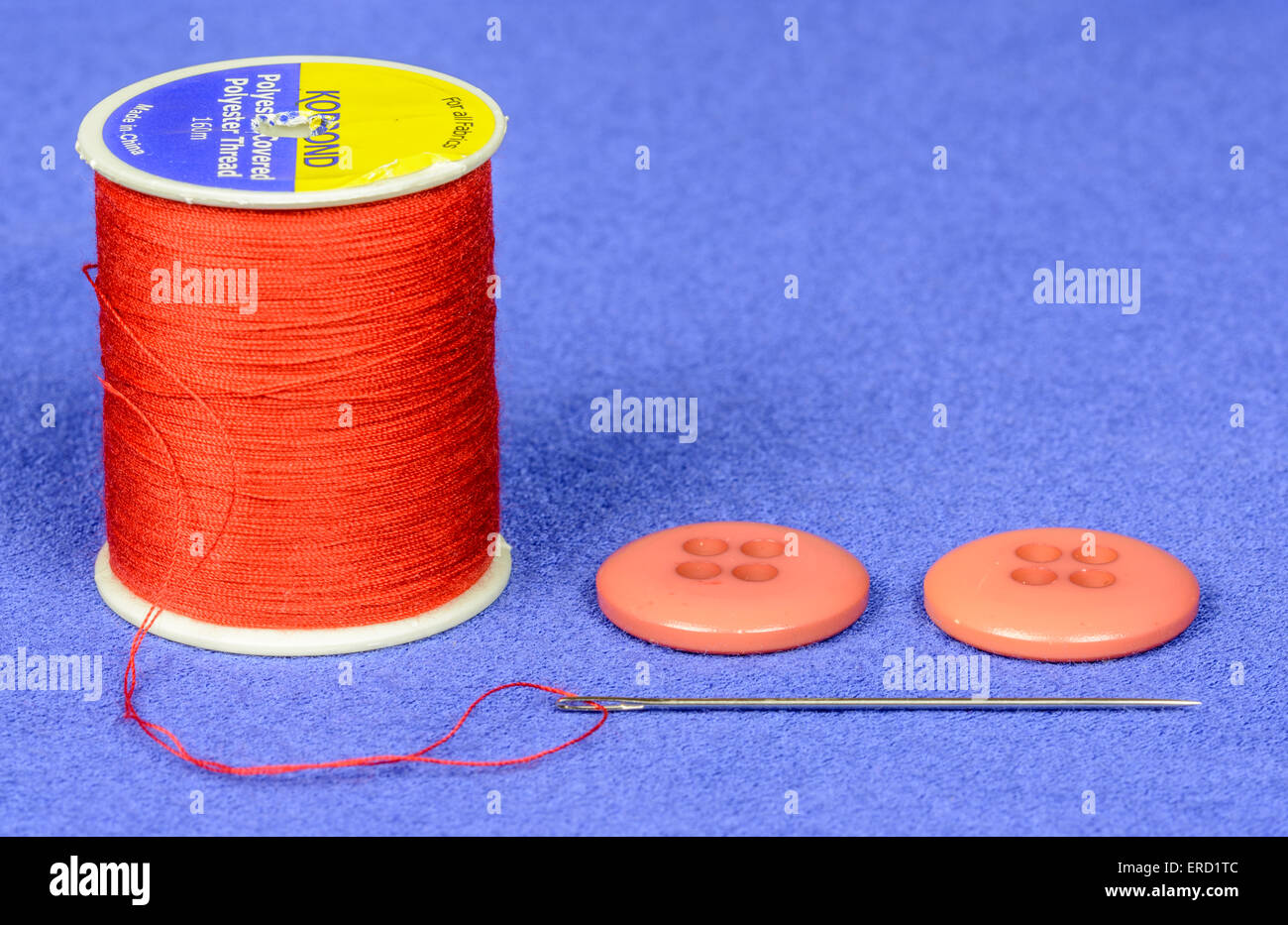 Closeup of a reel of red cotton with red buttons and a threaded sewing needle. - Stock Image