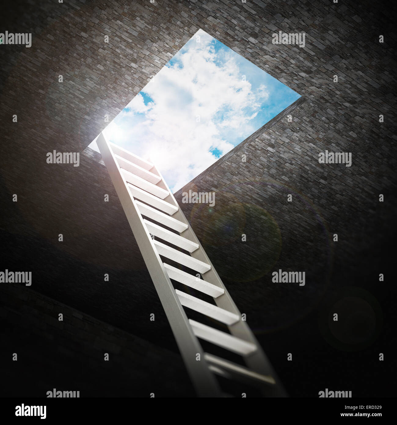 Ladder leading to the opening to the blue sky. - Stock Image
