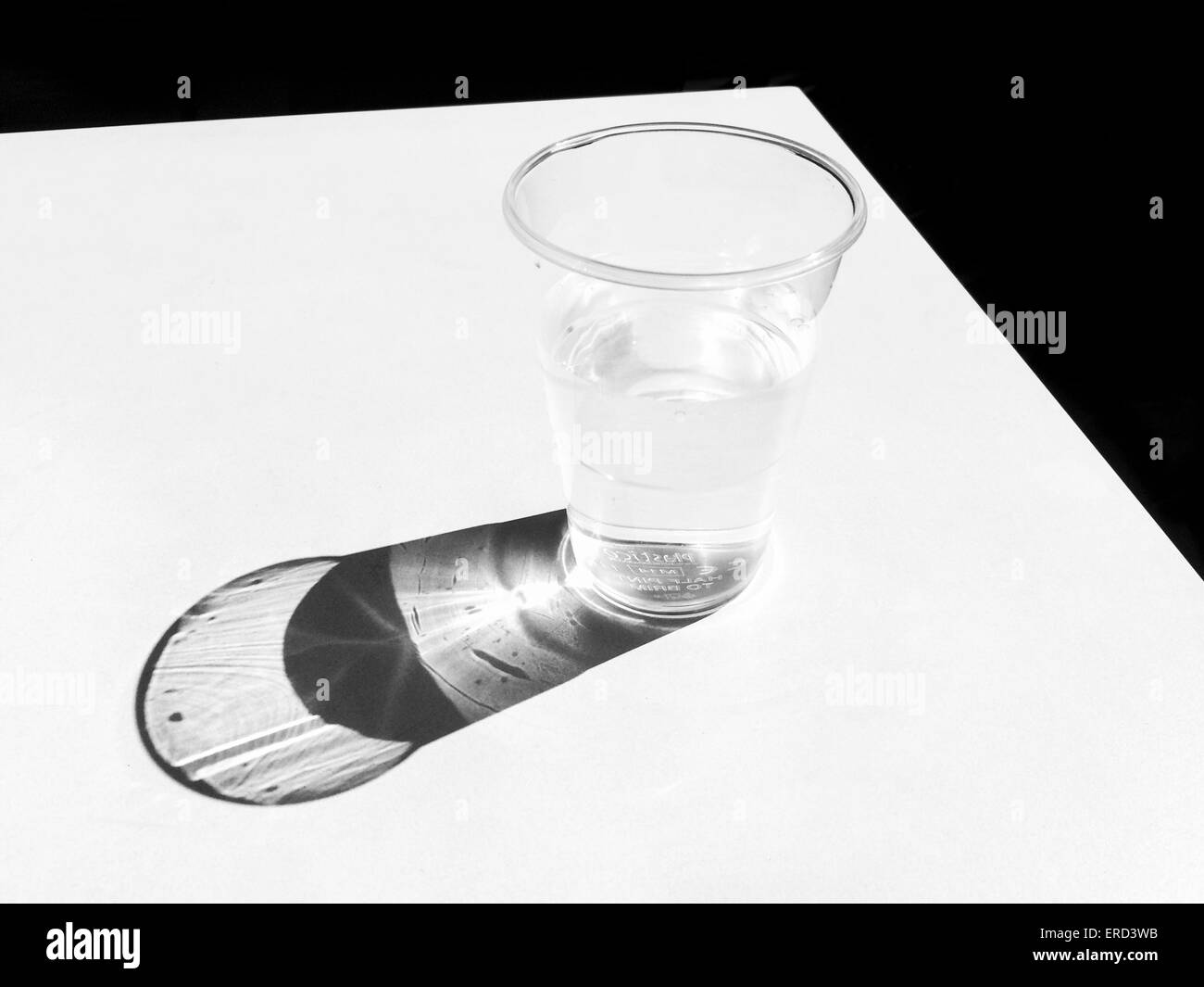 Sun casting a shadow of a beaker of water on a white table top in the UK - Stock Image