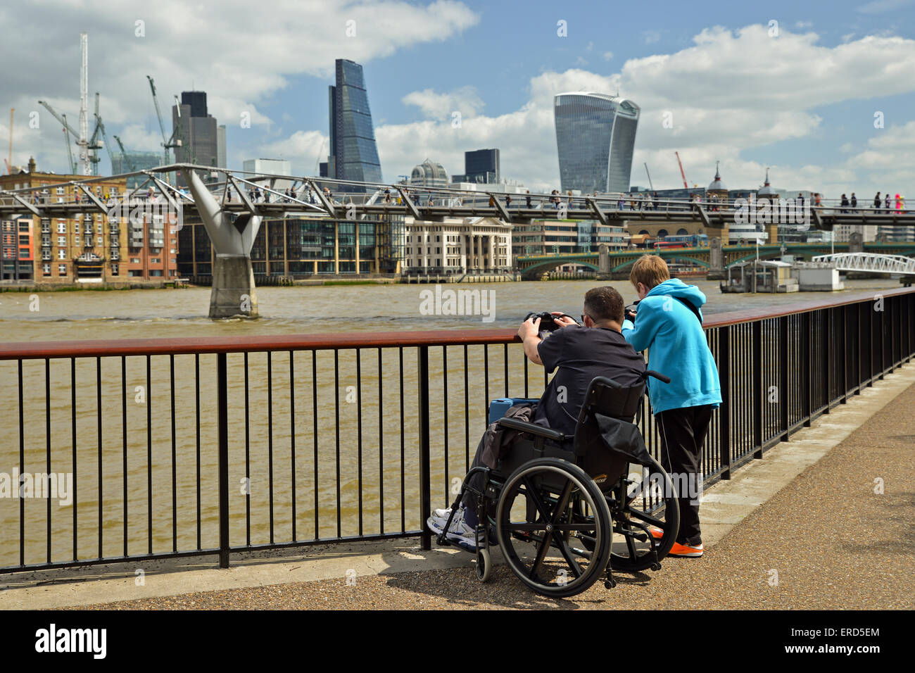 People taking pictures of the Millennium Bridge and the City beside the River Thames  London UK - Stock Image