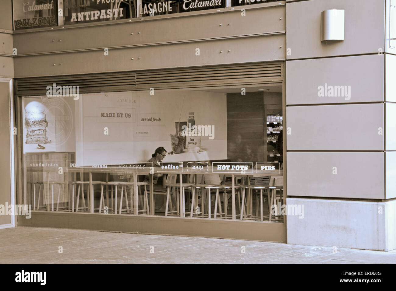 View through window of One person sitting in a cafeteria in London United Kingdom - Stock Image