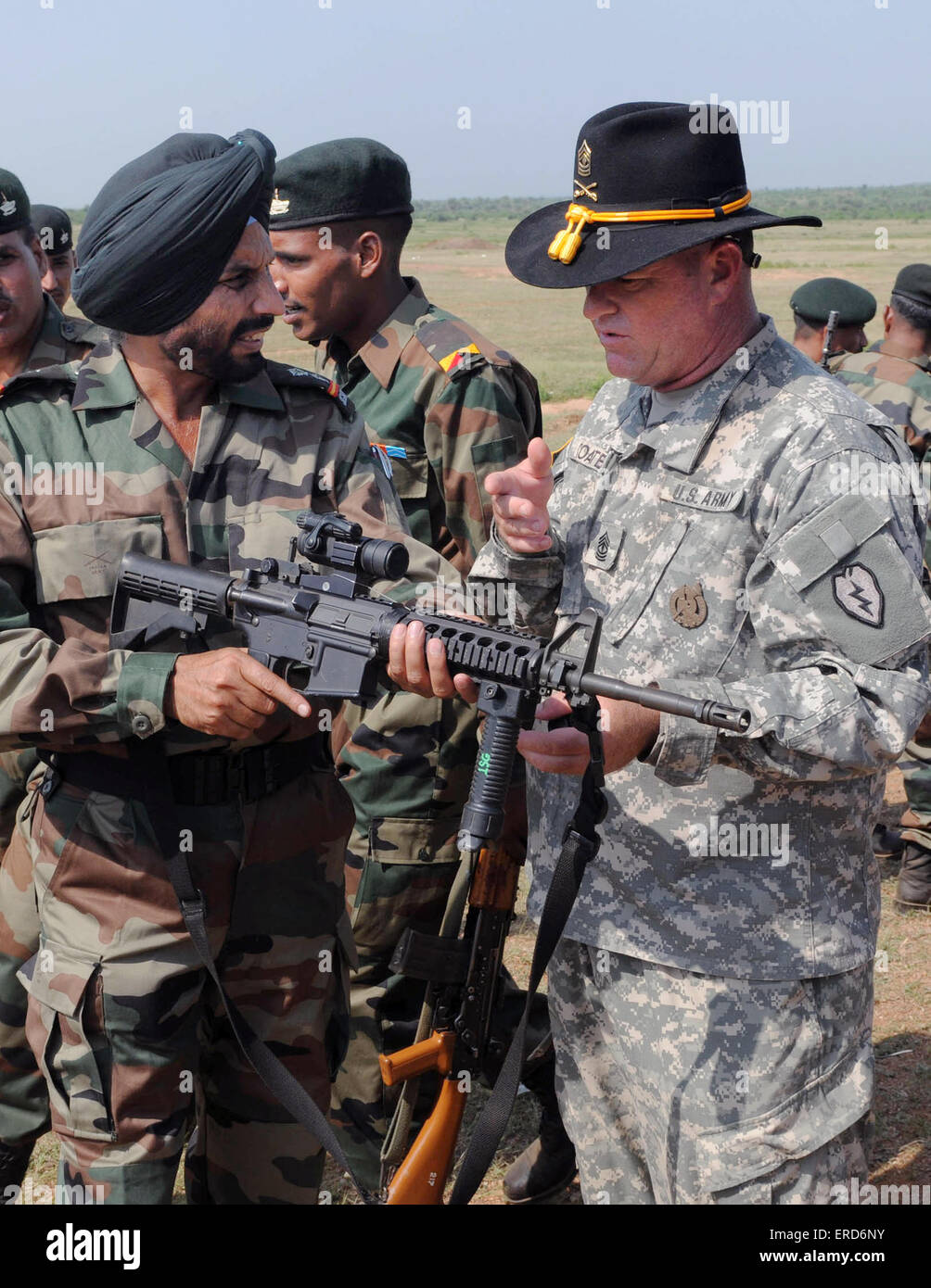 US Army 1st Sgt. Anthony Coates discusses the M4 carbine rifle with Indian Army Soldiers from the 94th Armored Brigade - Stock Image