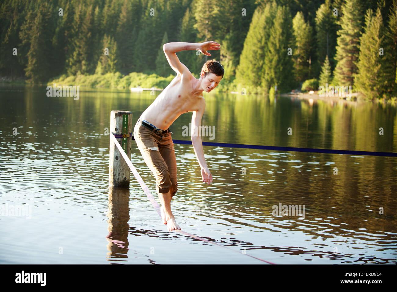 Josh Ayling walks a slack line at Lost Lake Park.  Whistler BC, Canada. - Stock Image