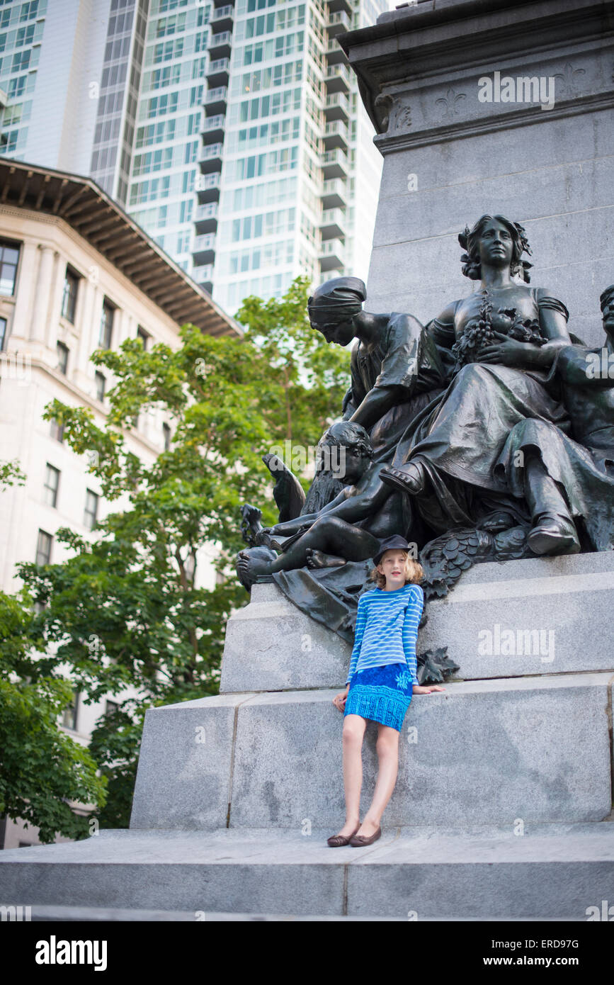 Family Fun in Montreal, Quebec, Canada. Downtown Montreal. Girl posing infront of statue. - Stock Image