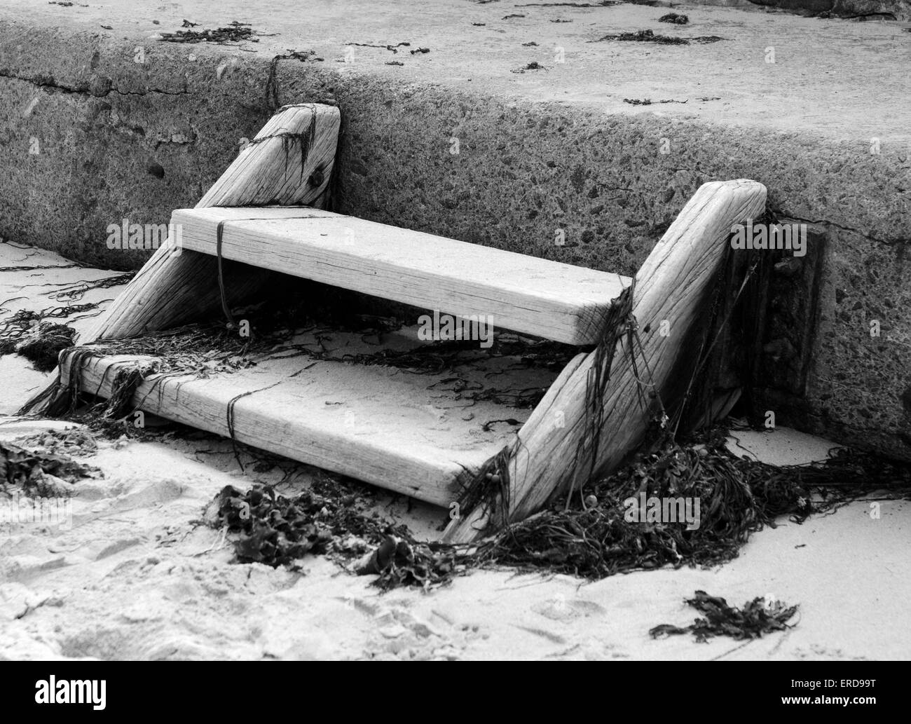 Wooden Steps on a sandy beach with seaweed - Stock Image