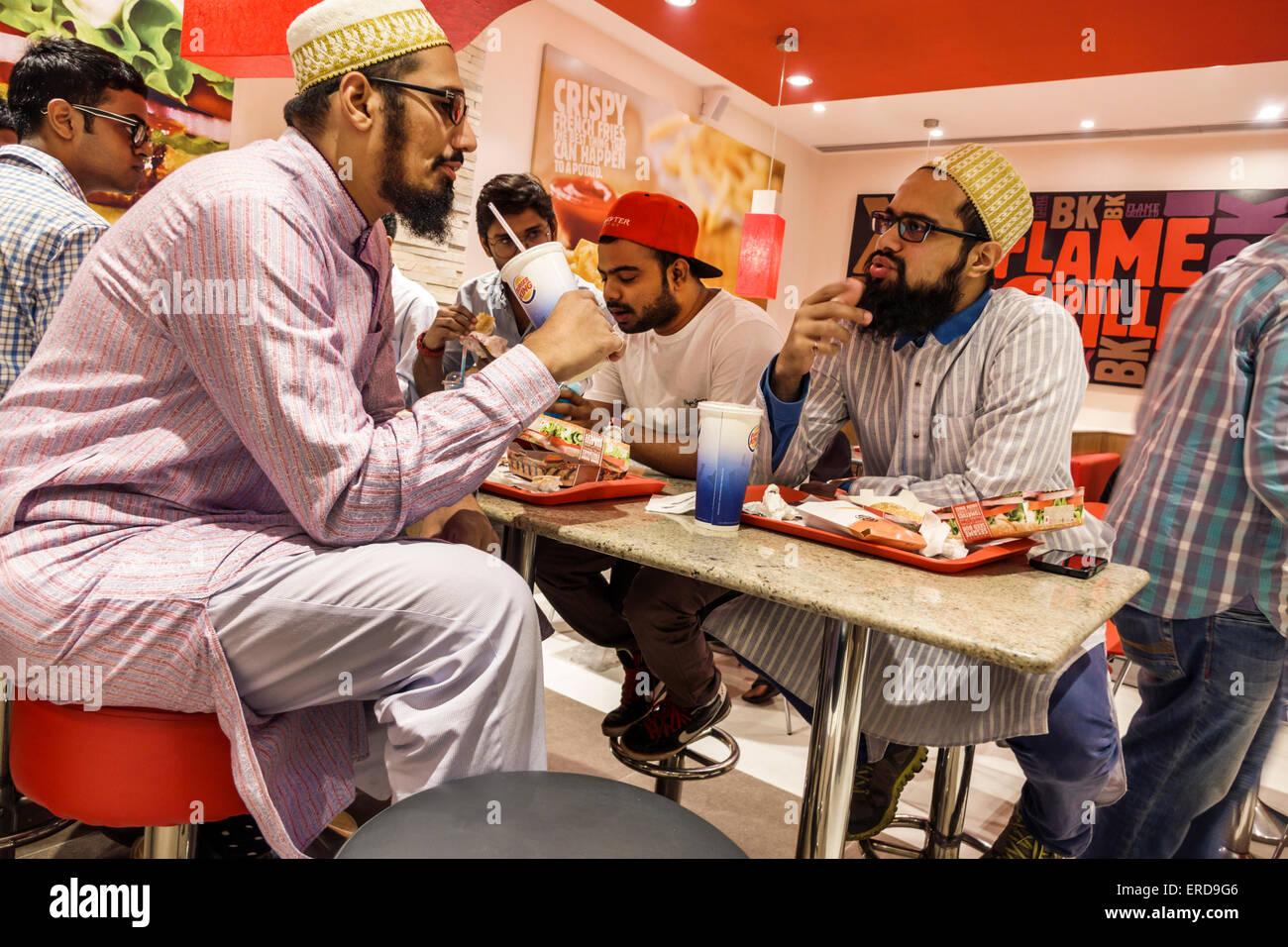 Mumbai India Asian Lower Parel High Street Phoenix mall inside restaurant Burger King fast food man friends sitting - Stock Image