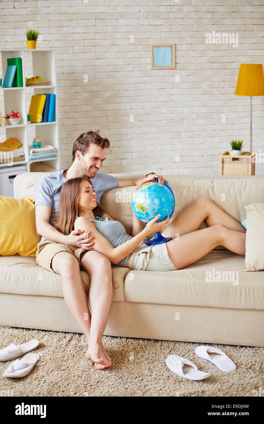 Happy couple with globe choosing place for spending honeymoon - Stock Image