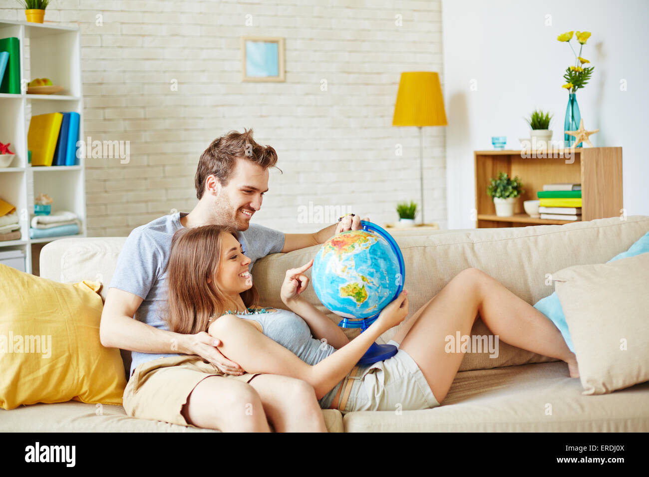 Happy couple with globe choosing place for summer rest - Stock Image
