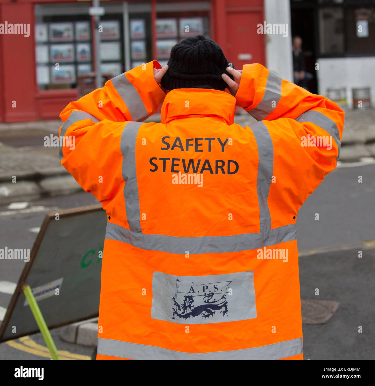Safety steward at a 10 kilometer running event wearing an orange high vis jacket - Stock Image