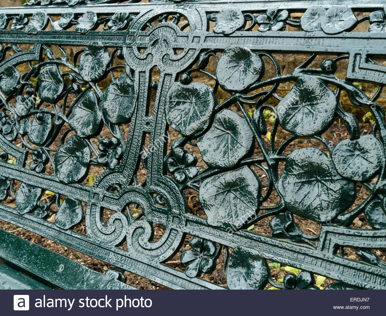 Floral pattern detail from green painted cast metal garden bench seat, Chatswoth, Derbyshire, England, UK. - Stock Image
