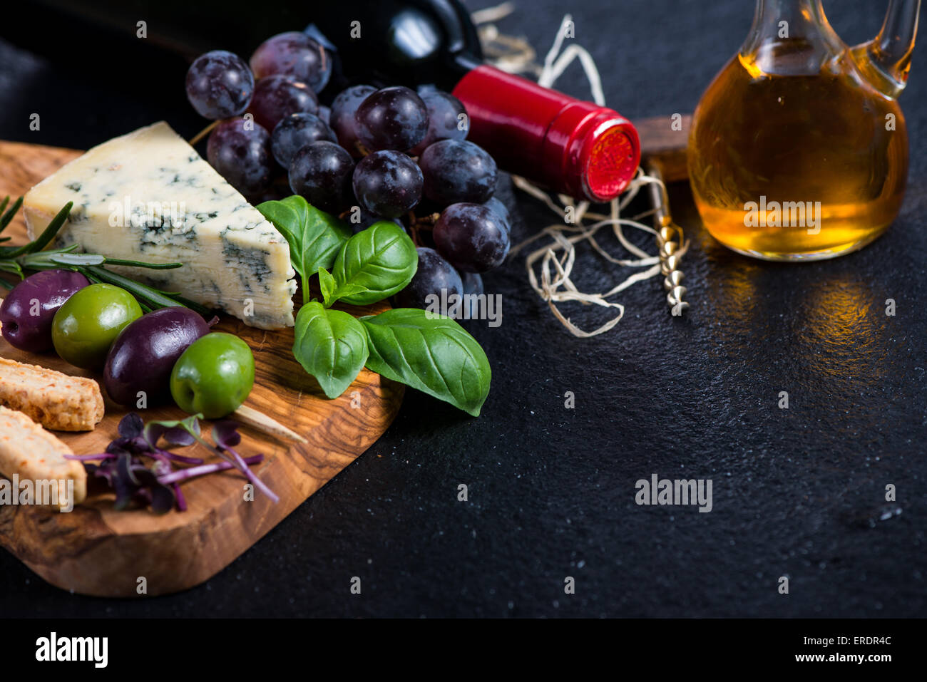 Tapas board with cheese,olives,grapes and red wine,food border background - Stock Image