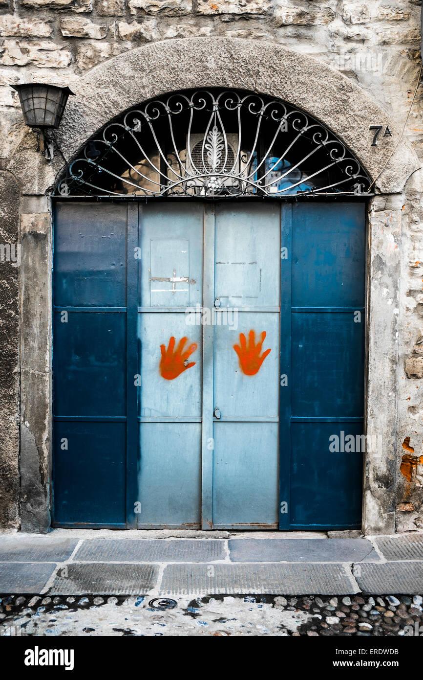 Old door with painted orange hand-prints Bergamo Lombardy Italy & Old door with painted orange hand-prints Bergamo Lombardy Italy ...