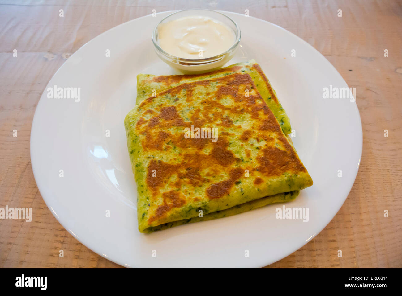Spinach pancakes with sour cream sauce, Vilnius, Lithuania, Europe - Stock Image