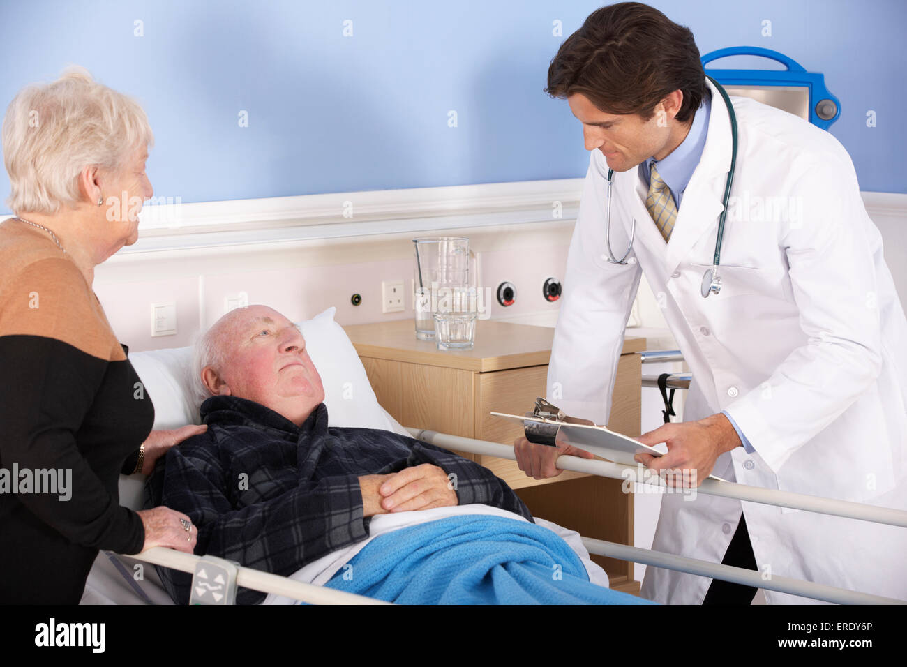 Doctor talking to senior couple in hospital - Stock Image