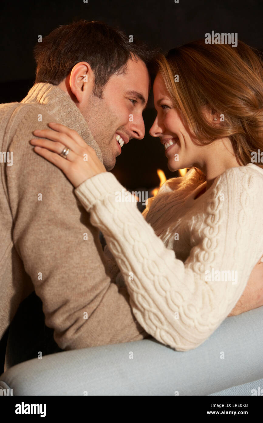 Romantic portrait couple in front of fire - Stock Image