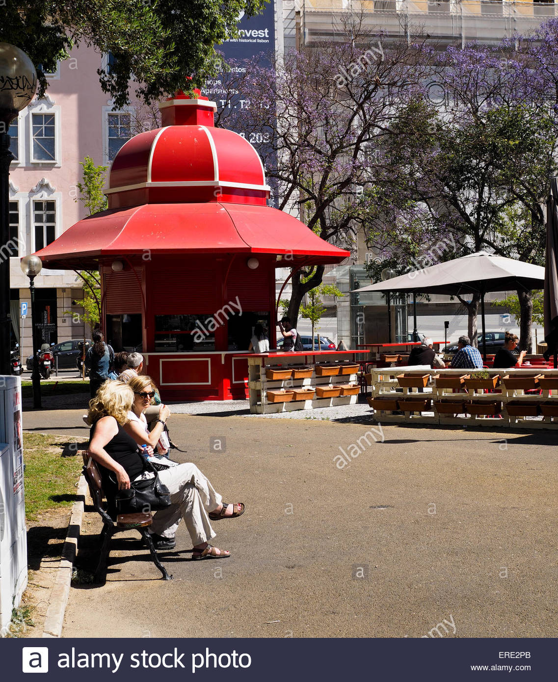 Ladies sitting on park bench in sunshine and Kiosk in Lisbon Stock