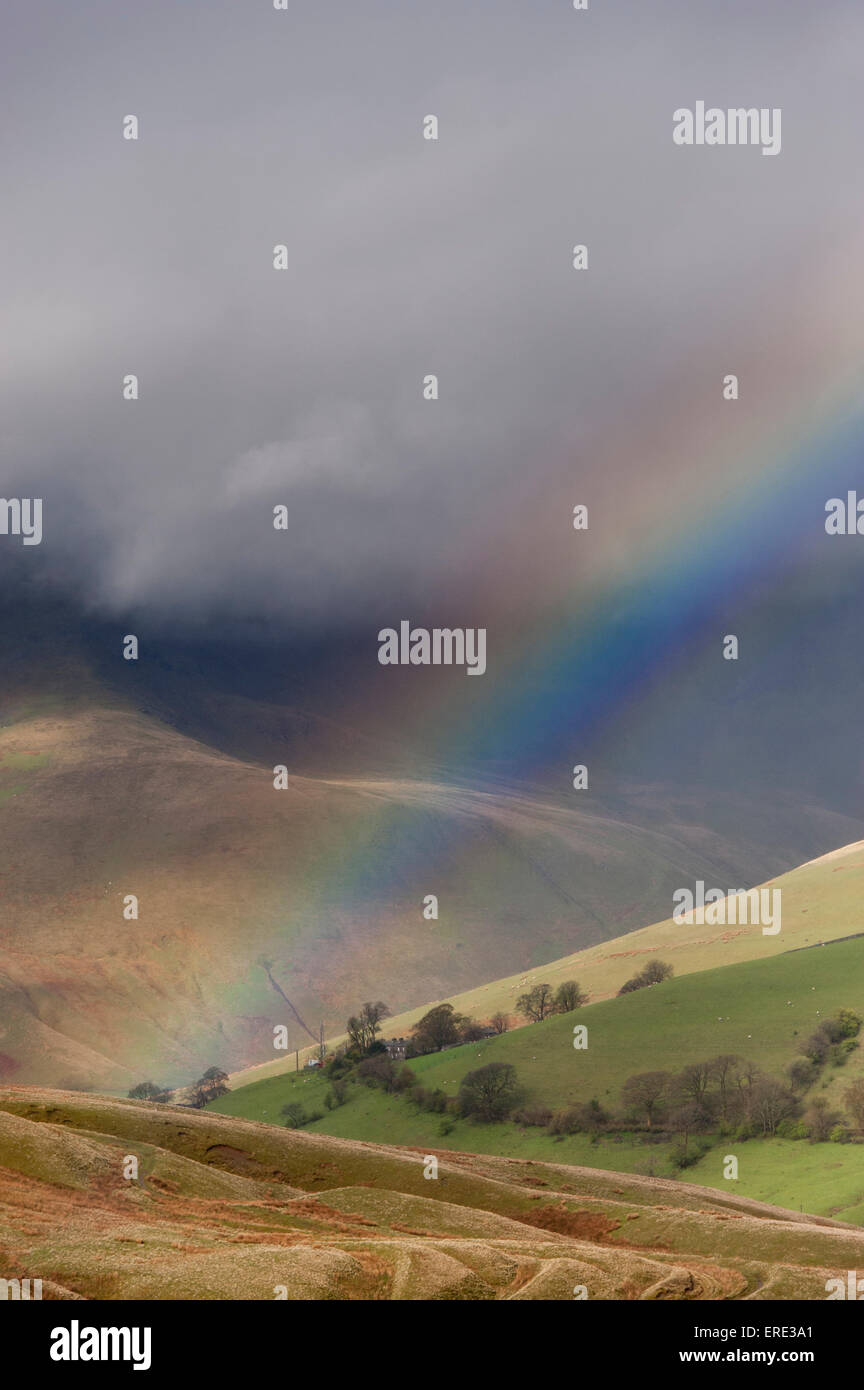 Rainbow in spring showers, over Cautley Crag in the Howgills near Sedbergh, Cumbria, UK. - Stock Image