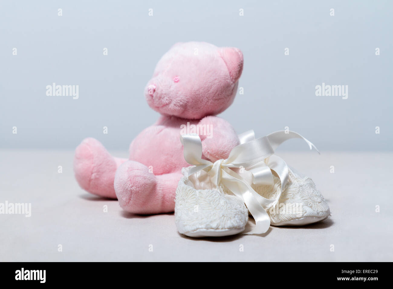 White lace baby booties and a cute pink teddy bear. - Stock Image