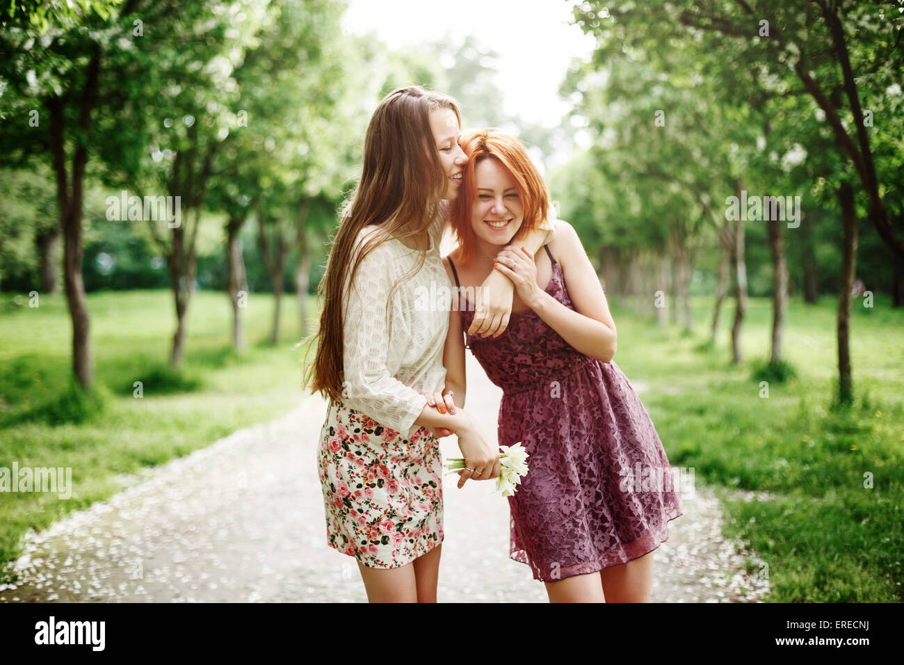 Two Young Happy Girls Having Fun in the Summer Park. Best Friends Laughing and Embracing. - Stock Image