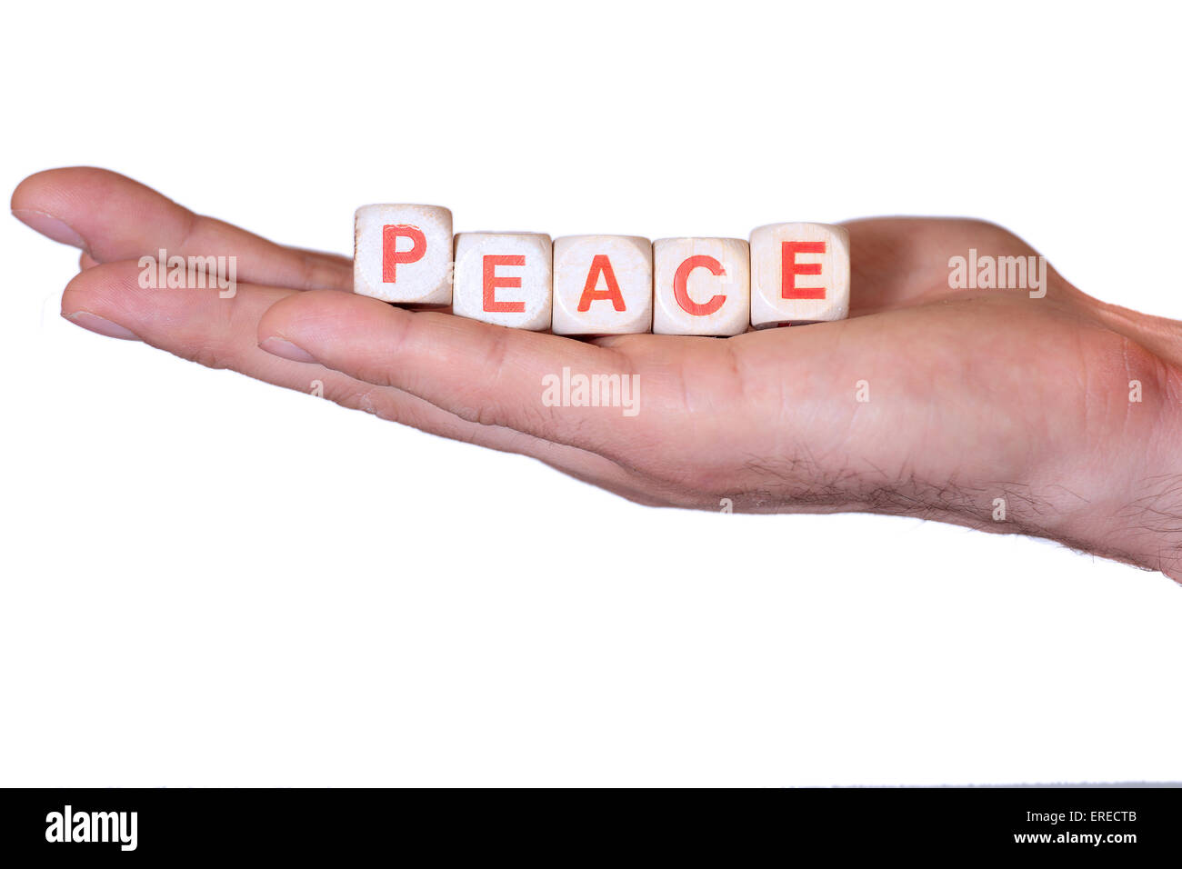 The word peace written with wooden dice on the he palm of the hand. Isolated on white background - Stock Image