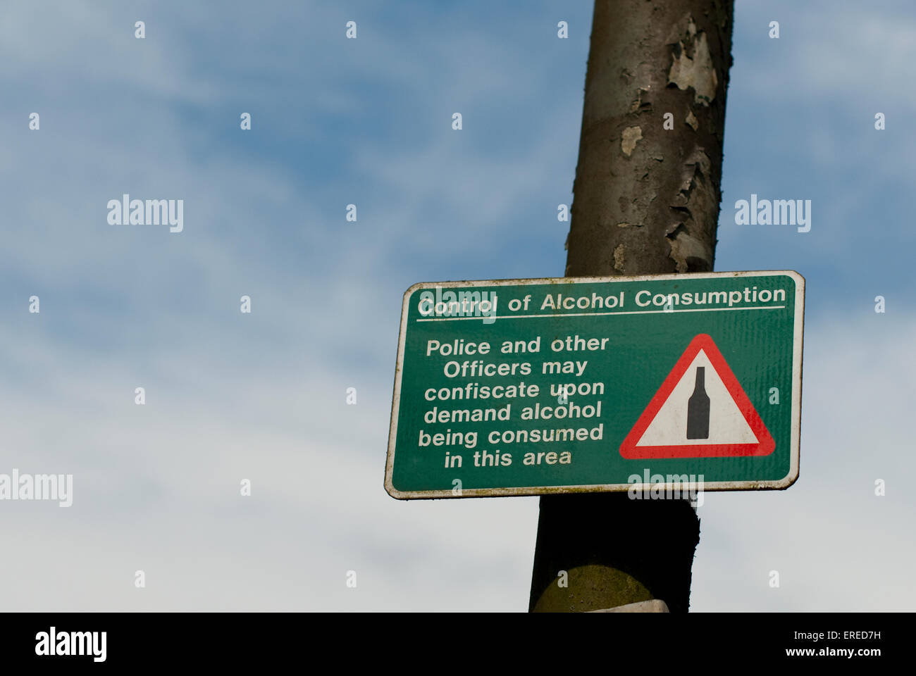 Documentary image of a control of alcohol consumption sign on a lamp-post with flaking paint against a blue sky. - Stock Image
