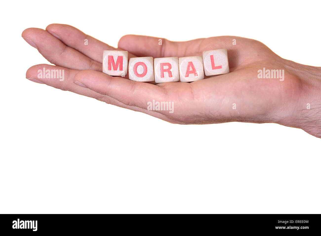 The word moral written with wooden dice on the he palm of the hand. Isolated on white background - Stock Image