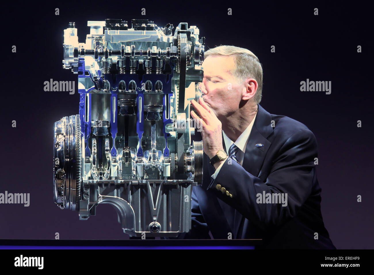 Ford CEO Alan R. Mulally kisses the 1.0-litre EcoBoost engine at the revealing ceremony at Ford Cologne plant, Germany, - Stock Image