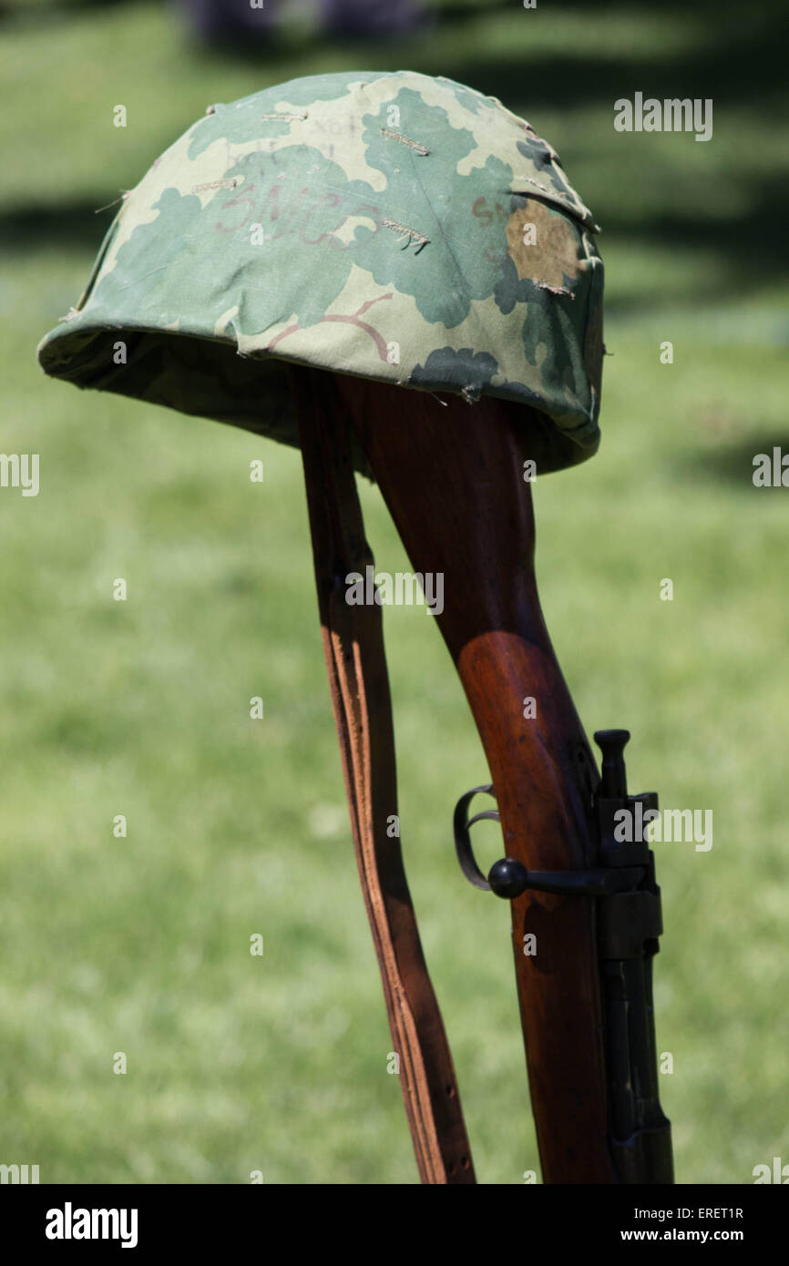 A warrior's helmet- an American GI helmet rests on a rifle stock at a USA Memorial Day service on Long Island New Stock Photo
