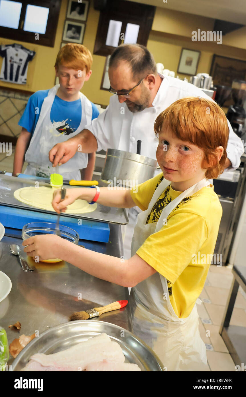 Boys having a cooking lesson in a traditional members only Basque influenced all male cooking club, San Sebastian, - Stock Image