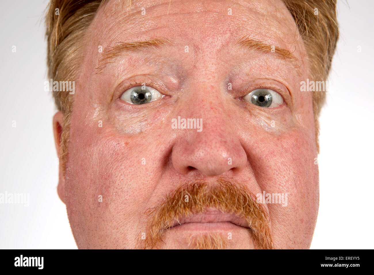 Close up of red haired man with a suspicious or skeptical expression on his face. - Stock Image