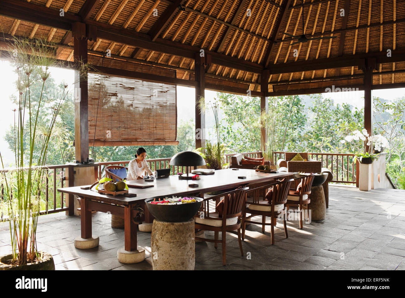 Balinese woman sits behind the desk at the reception area of Ubud Hanging Gardens, Bali, Indonesia. - Stock Image
