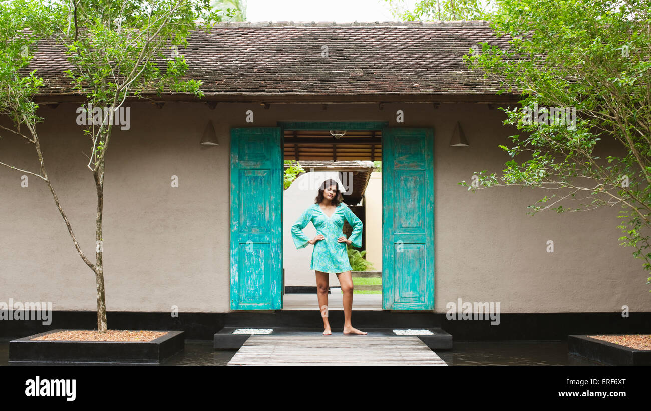 A young woman stands at the entrance of Sahana Spa, Saman Villas, Aturuwella, Bentota, Sri Lanka. - Stock Image