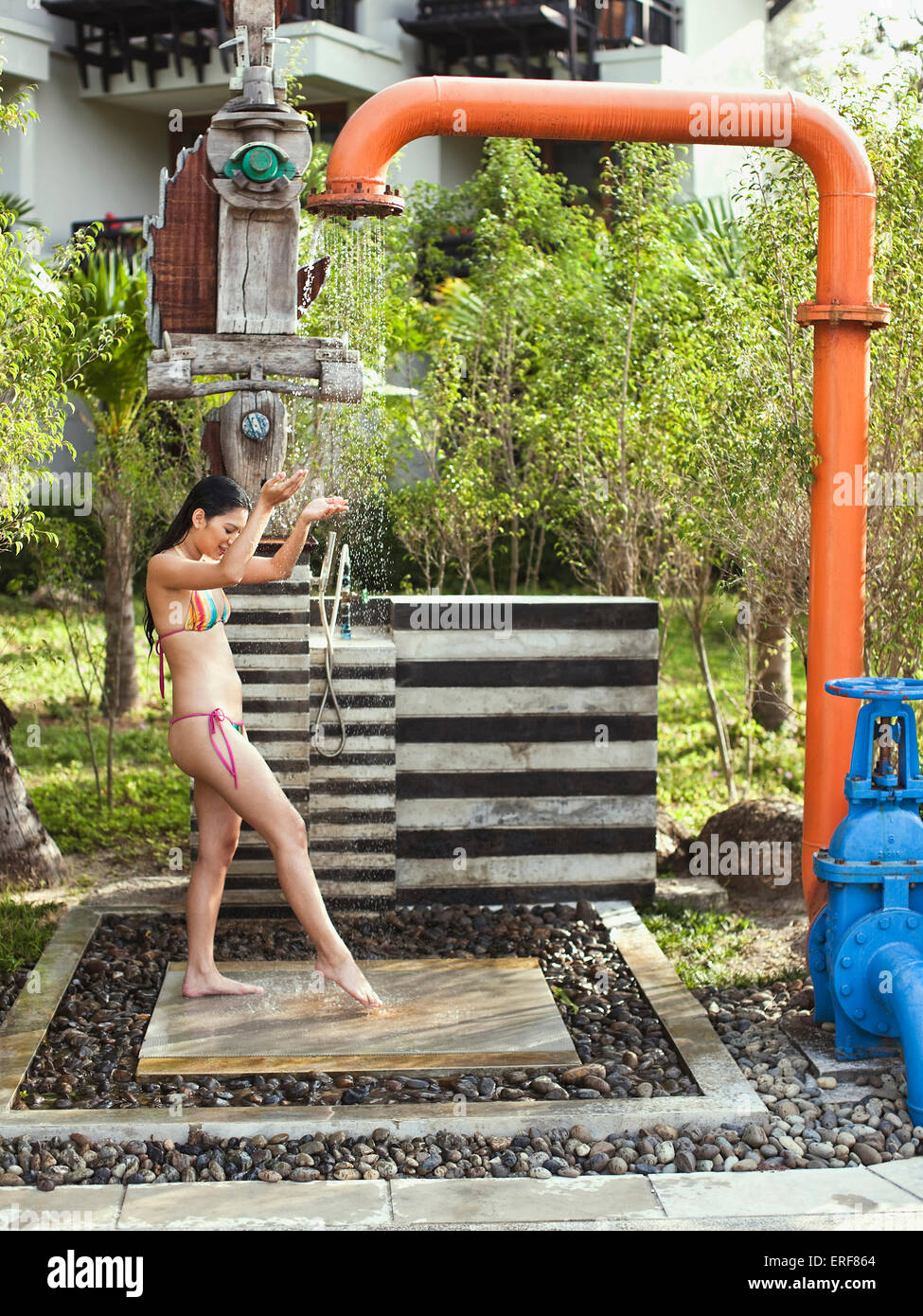 A woman showers under the pipe shower near the main pool at Indigo Pearl resort, Phuket, Thailand. - Stock Image